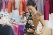 Asian woman looking holding up shirt at boutique — Foto Stock