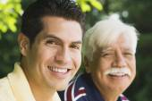 Hispanic man smiling with father outdoors — Foto Stock
