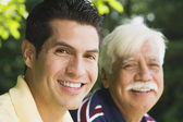 Hispanic man smiling with father outdoors — ストック写真