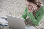Young girl lying on the floor with laptop — Stock Photo