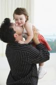 Hispanic father holding up and kissing young daughter — Stock Photo