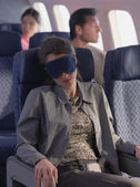 Young woman sleeping on airplane with eye mask — Stock Photo