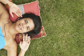 Young woman lying outside listening to music — Stock Photo