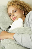 Woman sleeping with teddy bear in bed — Stock Photo