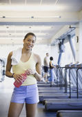 Woman at gym with water — Stock Photo
