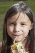 Young girl drinking out of a juice box — Stock Photo