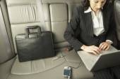 Businesswoman working in the backseat of a car — Stock Photo