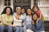 Female Hispanic family members sitting on the porch smiling — Stock Photo