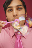 Businessman blowing bubbles — Stock Photo