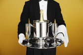 Waiter delivering champagne on silver platter — Stock Photo