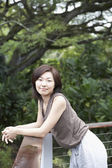 Asian woman leaning on balcony railing — Stock Photo