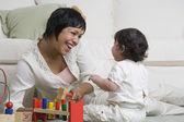 Hispanic mother and baby playing on floor — Stock Photo