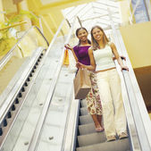 Girlfriends descend escalator in shopping mall — ストック写真