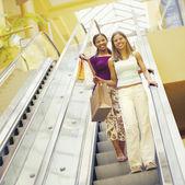 Girlfriends descend escalator in shopping mall — Stockfoto