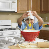 Young Hispanic boy cracking egg into bowl in kitchen — Stock Photo