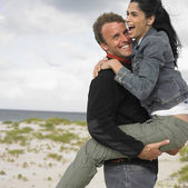 Multi-ethnic couple playing at beach — Stock Photo