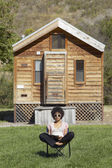 African American woman sitting in front of cabin — Stock Photo