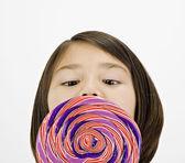 Asian girl licking lollipop — Stock Photo