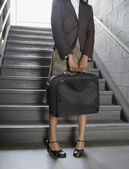 Businesswoman holding briefcase at bottom of stairs — Stock Photo