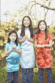 Three young Asian sisters holding fortune cookies — Stock Photo