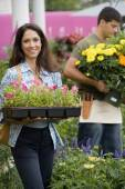 Hispanic woman carrying flowers at plant nursery — Stock Photo