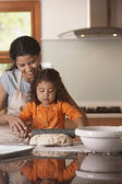 Mother and daughter rolling bread dough — Stock Photo