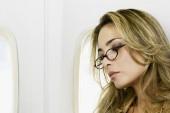 Woman wearing eyeglasses on airplane — Stockfoto