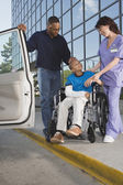 African boy in wheelchair leaving hospital with father — Stock Photo