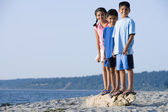 Hispanic siblings standing on driftwood at beach — Stock Photo