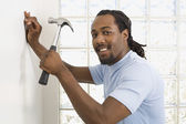 African man hammering nail into wall — Stock Photo