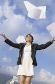 Asian businesswoman throwing papers in air — Stock Photo