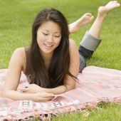 Asian woman playing solitaire on blanket in grass — Stock Photo