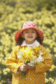 Young Hispanic girl in rain gear with flower bouquet outdoors — Stock Photo