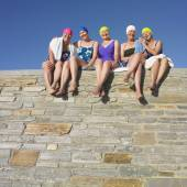 Group of senior women in bathing suits sitting on stone wall — Foto Stock