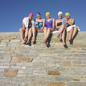 Group of senior women in bathing suits sitting on stone wall — Stockfoto