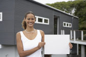 Mixed Race woman holding blank paper in front of house — Stock Photo