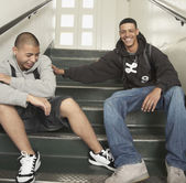 Two young men laughing on stairs at school — Stock Photo