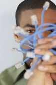 Young man holding Ethernet cables — Stock Photo
