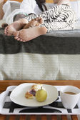 Couples feet laying in bed with breakfast — Stock Photo
