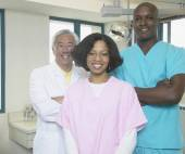 Senior Asian male dentist with African male and female dental assistants — Stock Photo