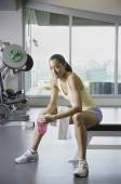 Woman sitting in weight bench at gym — Stock Photo