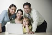 Hispanic family smiling with laptop — Stock Photo