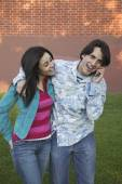 Young Hispanic couple using cell phone outdoors — Stock Photo