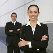 Hispanic businesswoman with coworker in background — Foto Stock