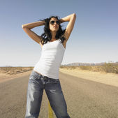 Woman standing in middle of deserted road with hands in hair — Stock Photo