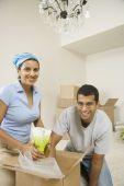 Indian couple unpacking moving boxes — Stock Photo