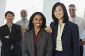Two businesswoman with co-workers in the background — Stock Photo