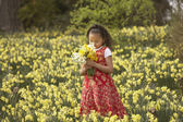 Young Hispanic girl smelling picked flowers outdoors — Stock Photo
