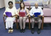 Group of people reading paperwork while sitting in waiting room — Stock fotografie