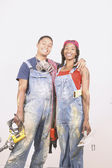 Couple in paint spattered overalls — Stock Photo